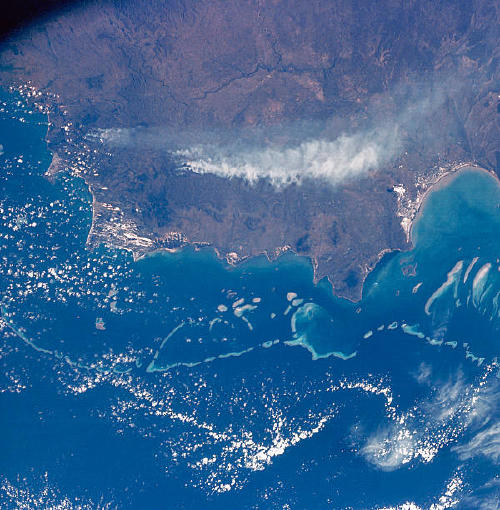 a view of the great barrier reef and the smoke from space