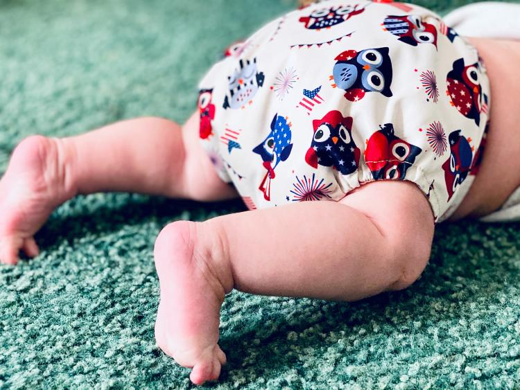 There\'s the bottom of a baby wearing a bulky, cloth diaper with an owl design.