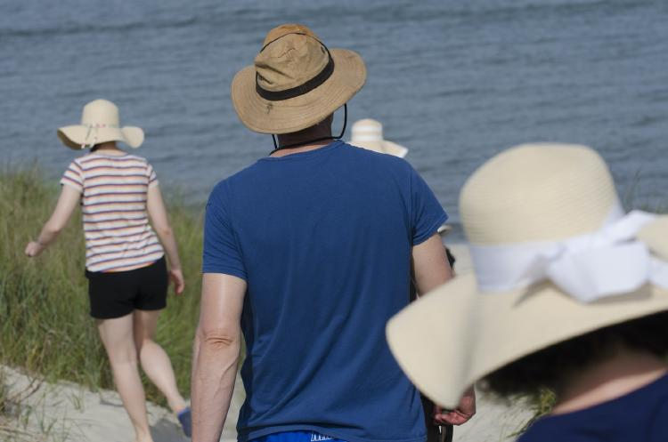 Family all wearing floppy  hats on the beach