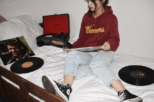 Girl sitting on a bed filled with vinyls and a record player
