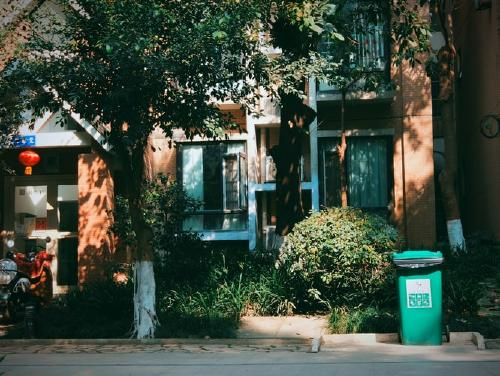 front view of a house and a green trash bin outside