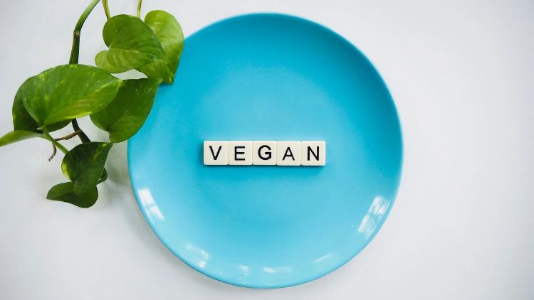 scrabble tiles speling vegan in blue ceramic plate