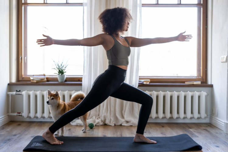 afroamerican woman practicing yoga at home with her dog