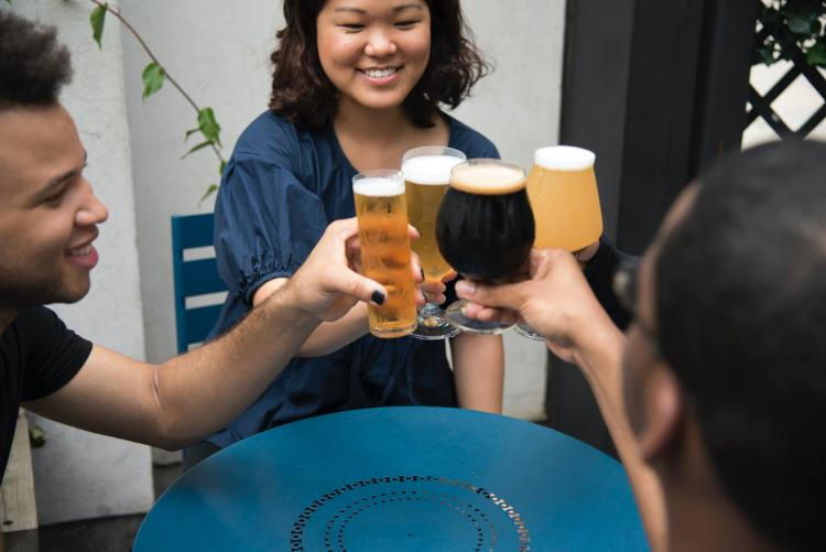 three people toasting with beers