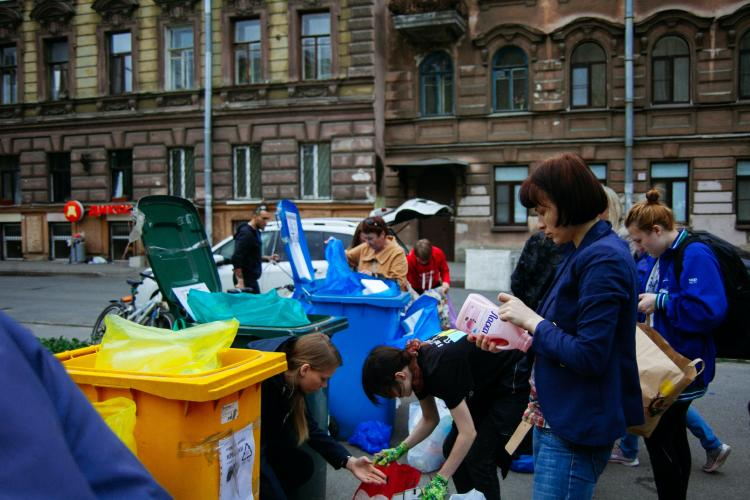 People approaching different containers for waste