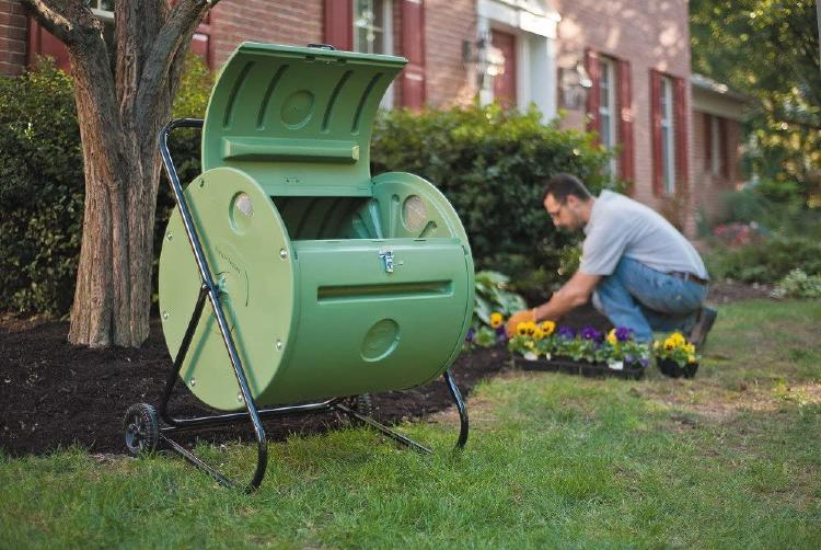 There\'s a man next to the composter doing some gardening