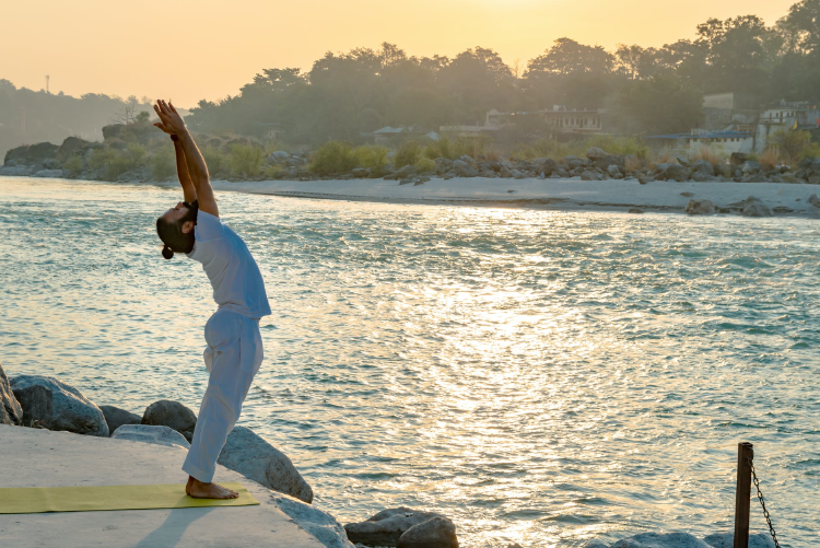 man in white t-shirt and pants doing the sun salutation