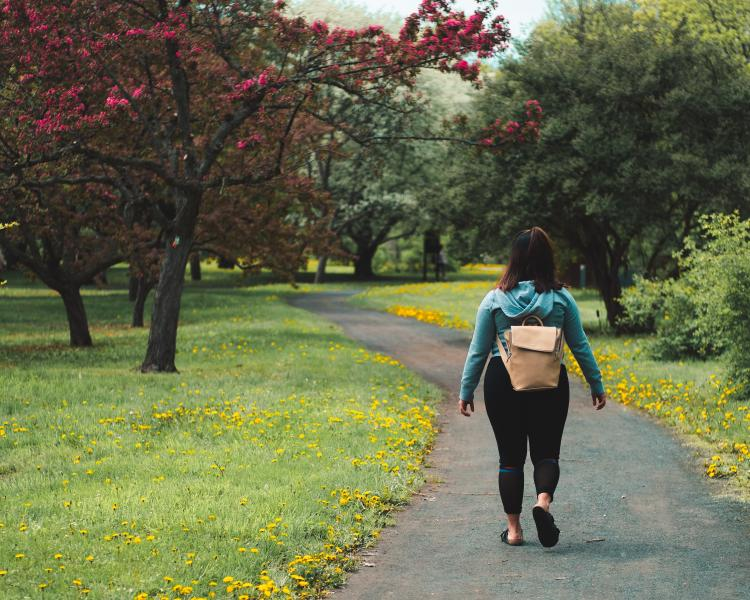 There\'s a woman walking in a park.