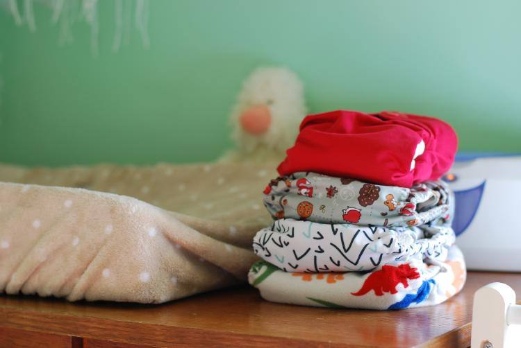 Four cloth diapers piled up on each other, with various colors and designs.