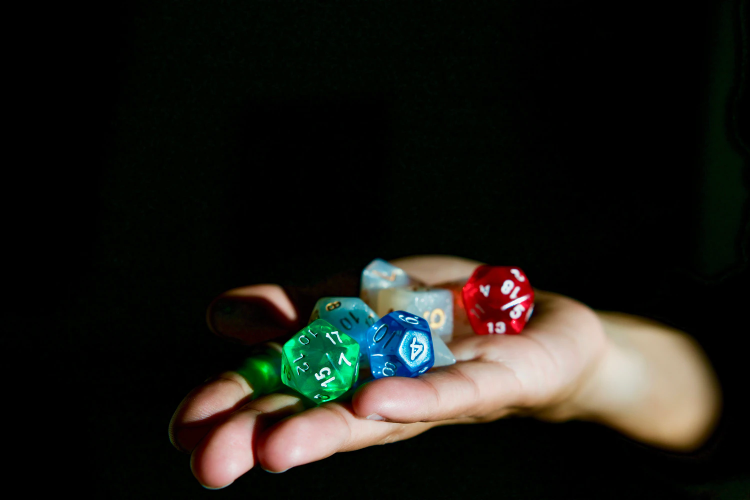 person holding hexagonal dices