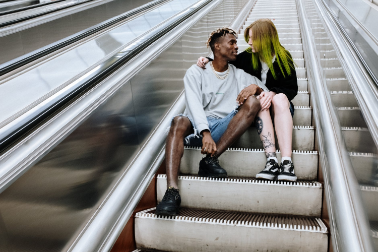 heterosexual couple sitting on stair looking at each other tenderly