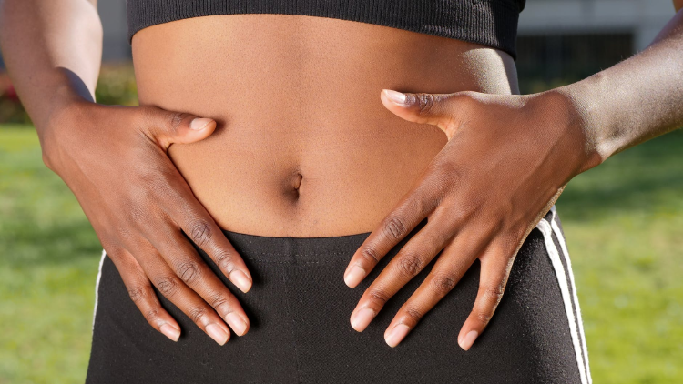 black woman with both hands on their belly