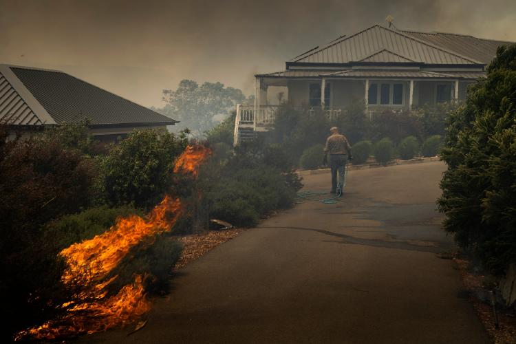 A man defending his house from the flames-82d6-4a54-8f37-25edb74e1660-superJumbo