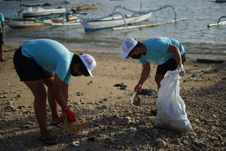 Two young people picking trash from a beach
