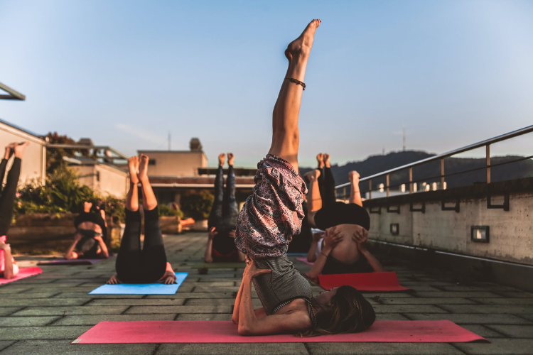 group of women doing yoga on a rooftop