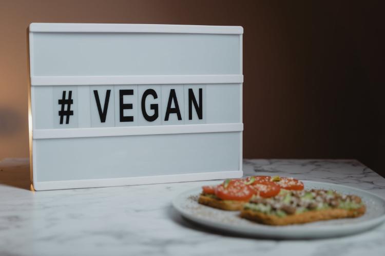 white and black sign reading vegan
