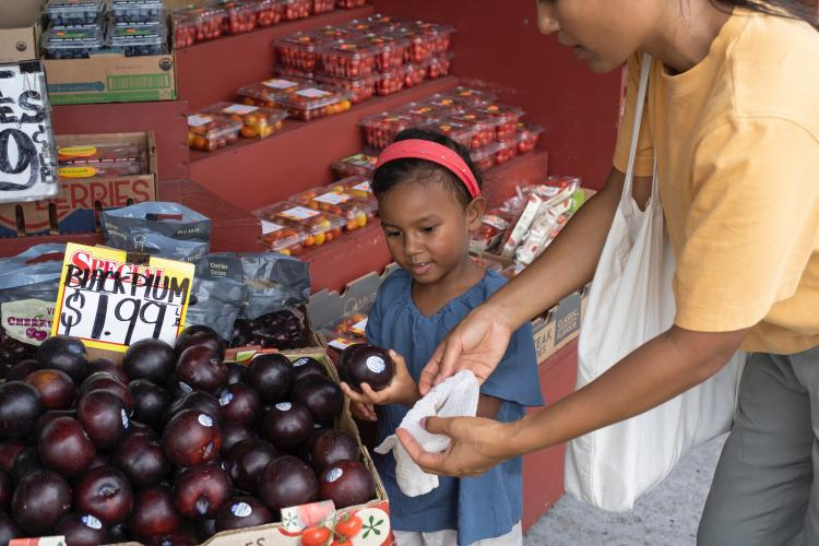 Girl and mom shopping for fruits
