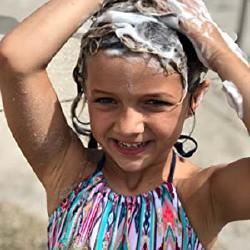 A little girl washing her hair with the Argan Vegan Shampoo Bar