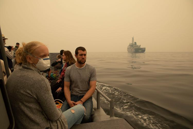 people on a navy boat being evacuated