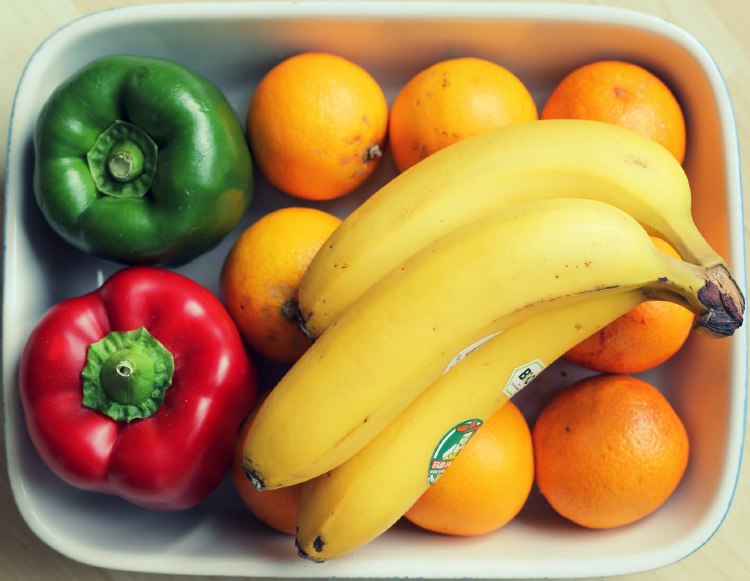 top image of bananas, peppers and oranges on a rectangular dish