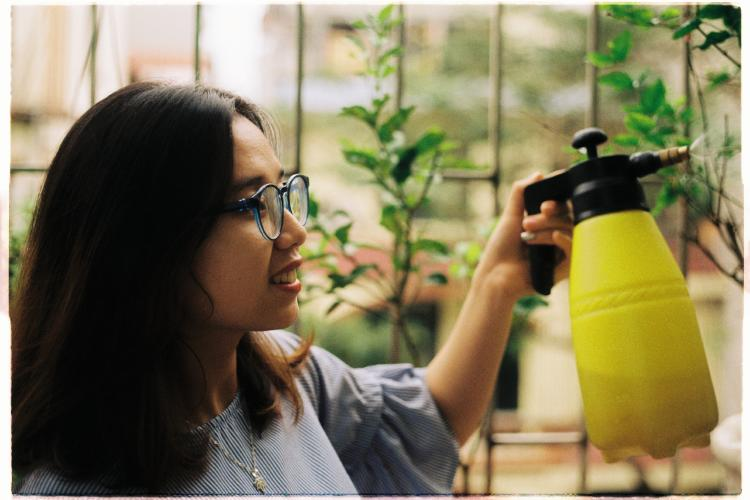 Joyful Girl watering plants with a spray bottle