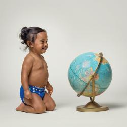 Girl wearing a Charlie Banana Cloth Diaper next to a globe