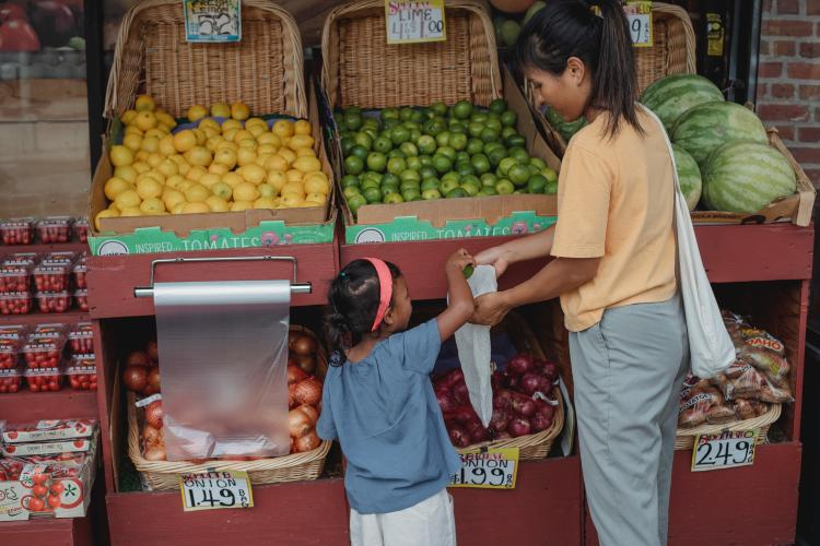 A little girl and her mom shopping in a fruit market