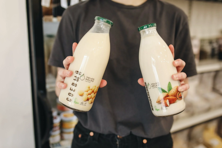 person holding a bottle of plant-based milk in each hand