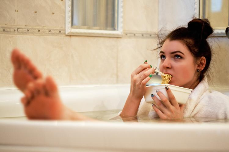 a girl eating pasta on a tub