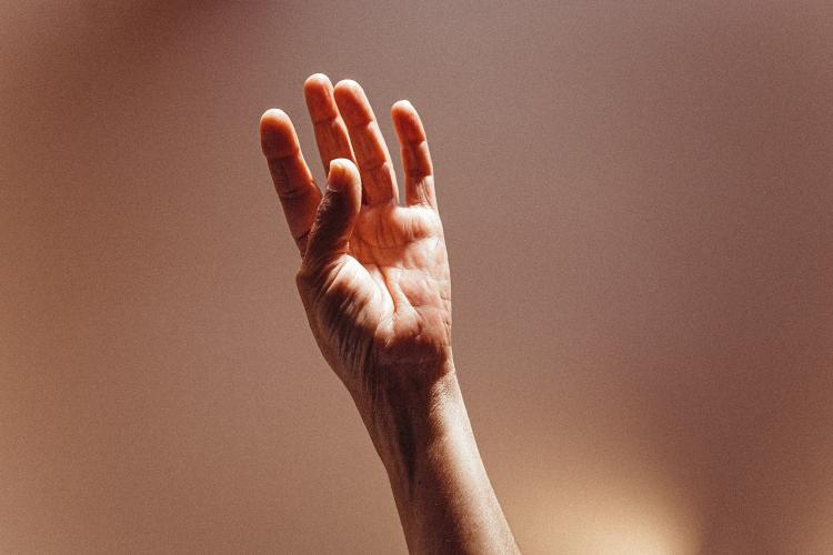 A hand facing a blurry background