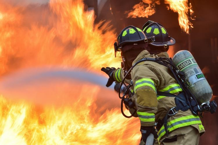 Two firefighters putting down a fire
