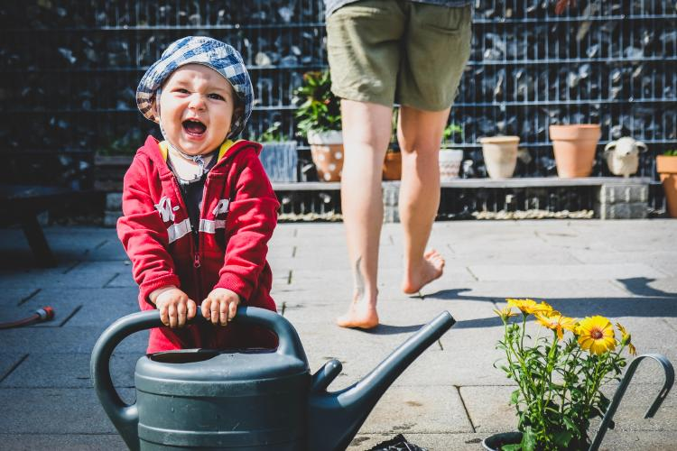 Baby girl smiling while holding a watering can