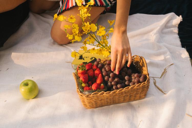ethnic woman picking fruit from a rectangular brown wicker basket