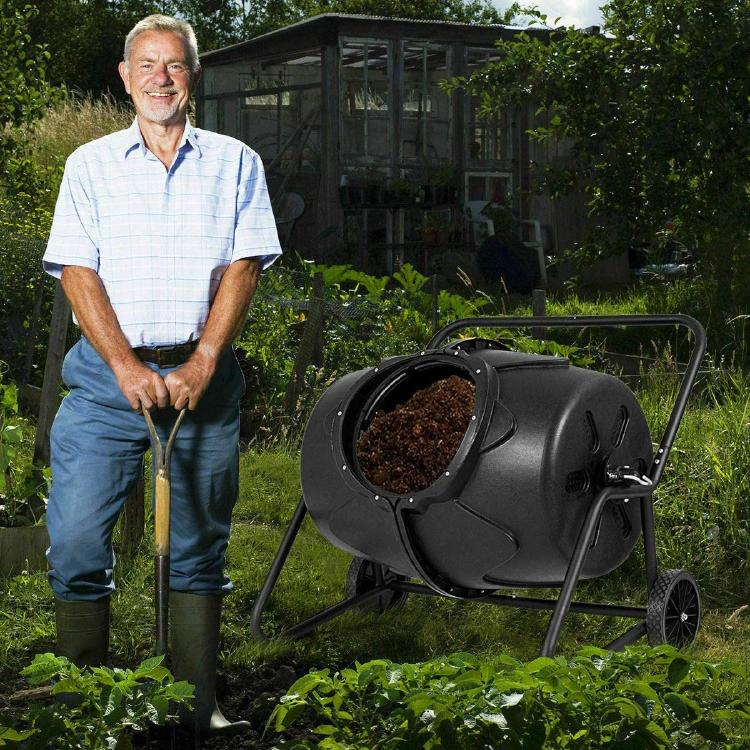 Man in his garden with the compost tumbler