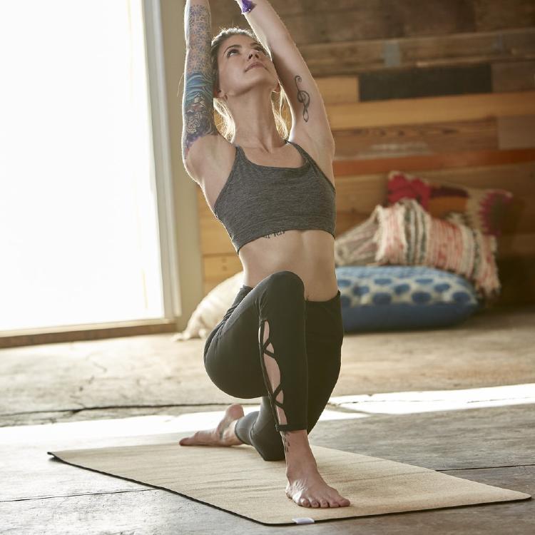 woman doing yoga on a performance cork yoga mat