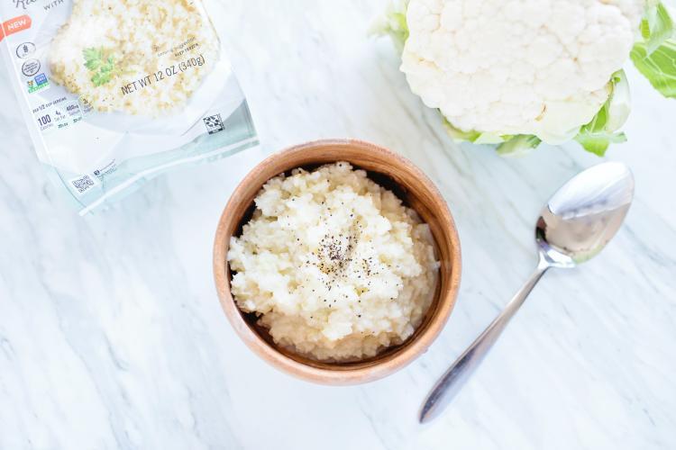 a cauliflower rice dish a cauliflower and some vegan cheese