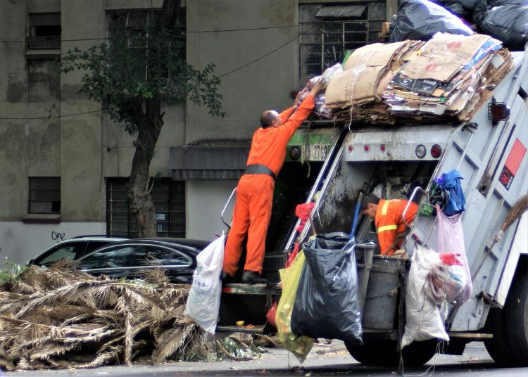 municipal workers lifting garbage on a truck