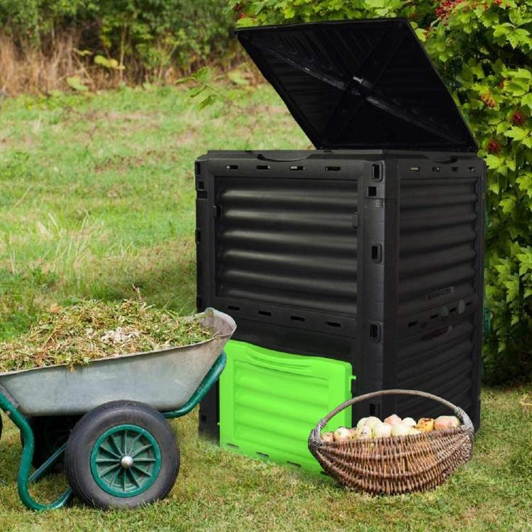 The EJWOX composter next to basket with food waste and next to a wheelbarrow.