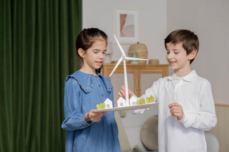 A girl ans a boy hold a miniature windmill